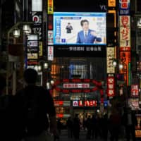 REUTERS | A LARGE TV SCREEN ON A BUILDING SHOWS PRIME MINISTER SHINZO ABE DECLARING A STATE OF EMERGENCY, AT TOKYO'S FAMOUS  KABUKICHO ENTERTAINMENT DISTRICT ON APRIL 7.