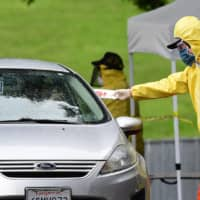 A driver receives a COVID-19 test kit at a coronavirus mobile testing site at Lincoln Park in Los Angeles, California on Thursday as COVID-19 antibody testing begins at undiscolsed locations across Los Angeles County. | AFP-JIJI