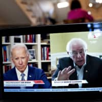 Sen. Bernie Sanders speaks as former Vice President Joe Biden listens during a virtual event on Monday. Sanders endorsed Biden during the joint livestream, saying that Americans of all political affiliations should back the former vice president.    BLOOMBERG