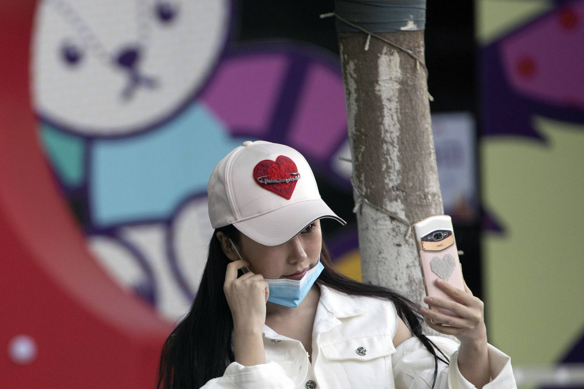 A woman lowers her mask briefly for a selfie in Wuhan, in central China's Hubei province, on Monday. | AP