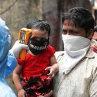 A doctor scans residents from Dharavi, one of Asia's largest slums, with an infrared thermometer in Mumbai on Saturday.  | REUTERS
