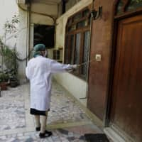 A doctor uses a piece of wood to ring a doorbell during door-to-door checks for COVID-19 symptoms in the Nizaumuddin area of New Delhi last Wednesday.  | REUTERS