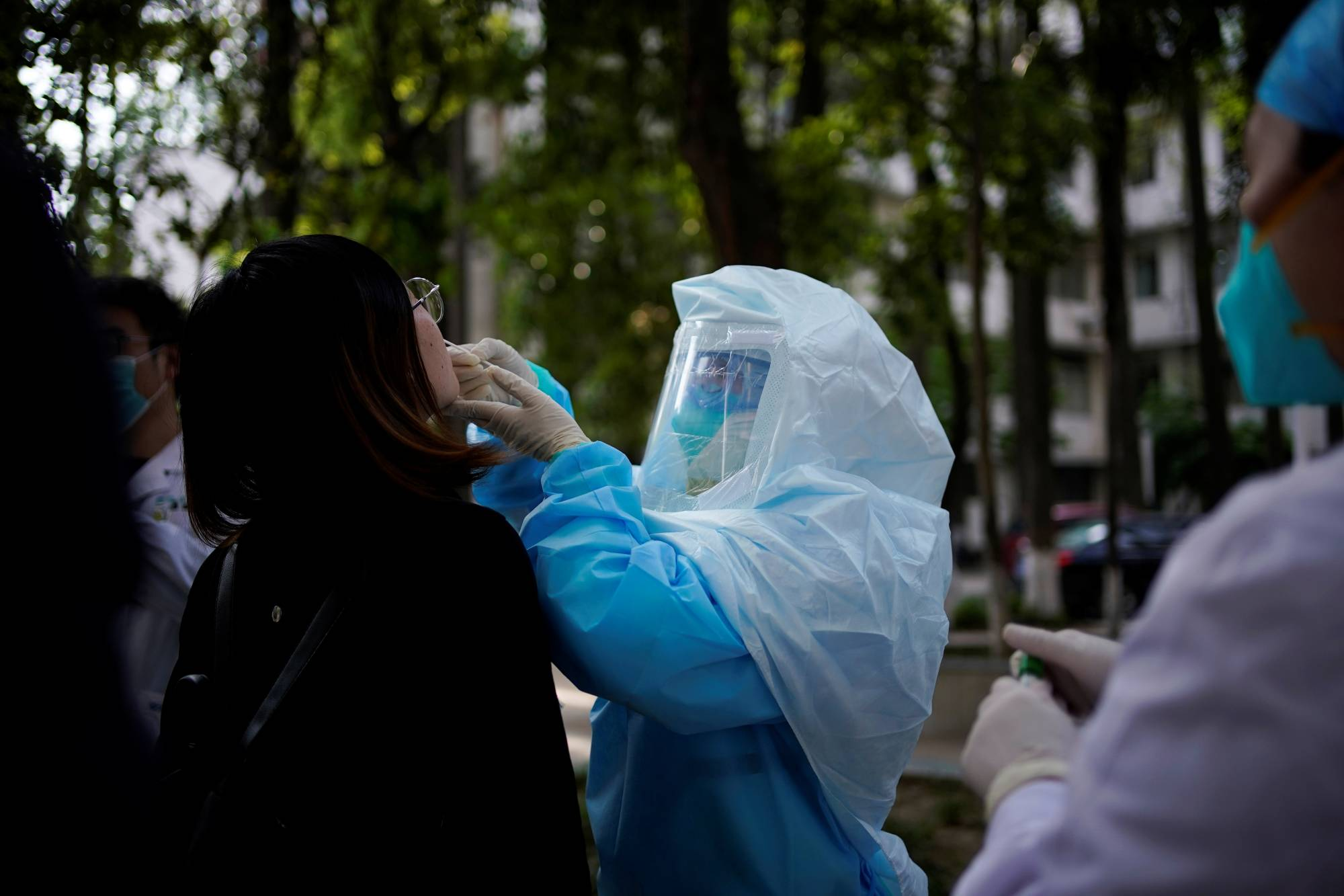 A woman receives a nucleic acid test for COVID-19 on a street near a hospital in Wuhan, China, on Monday.   REUTERS