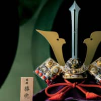 Swordsmith: This pure-silver kabuto helmet, titled 'Ken' ('Sword'), was made by the late Takehiko Seki II, a gold and silver craftsman recognized as a Master of Traditional Arts by the national government. The sword-shaped maedate frontal ornament, traditionally believed to ward off harmful forces, rises straight up. The kabuto helmet embodies hopes that boys will grow up healthy, strong and successful.  | JUN NAKAMURA