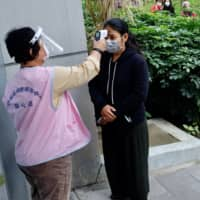 A masked local resident has her temperature checked as people line up to buy face masks from vending machines at the Xinyi District Health Center in Taipei on Tuesday.   AFP-JIJI