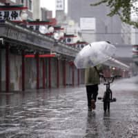 A man walks along a deserted street inTokyo's Asakusa district on Monday. Prime Minister Shinzo Abe declared a state of emergency last week for Tokyo and six other prefectures to help prevent the spread of COVID-19. | AP