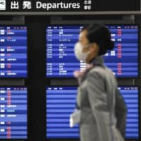 A departure board at Narita Airport near Tokyo shows most flights canceled on April 3 amid the spread of COVID-19. | KYODO