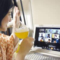 Company employee Chiaki Michibayashi takes part in an online drinking session at her home in Funabashi, Chiba Prefecture, on April 8. | KYODO