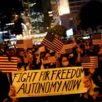 Anti-government demonstrators march in protest against the invocation of emergency laws in Hong Kong in October. | REUTERS