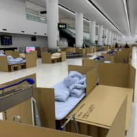 Cardboard boxes replace hotel rooms at Narita as Japan struggles with returnees