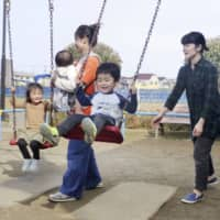 A couple play with their children in a park in Funabashi, Chiba Prefecture, in March. | KYODO