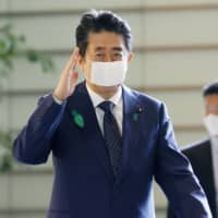 Prime Minister Shinzo Abe arrives at his office in Tokyo on Thursday. | KYODO