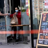 An employee brings take-out to a customer at a restaurant in Washington on Thursday.  | BLOOMBERG