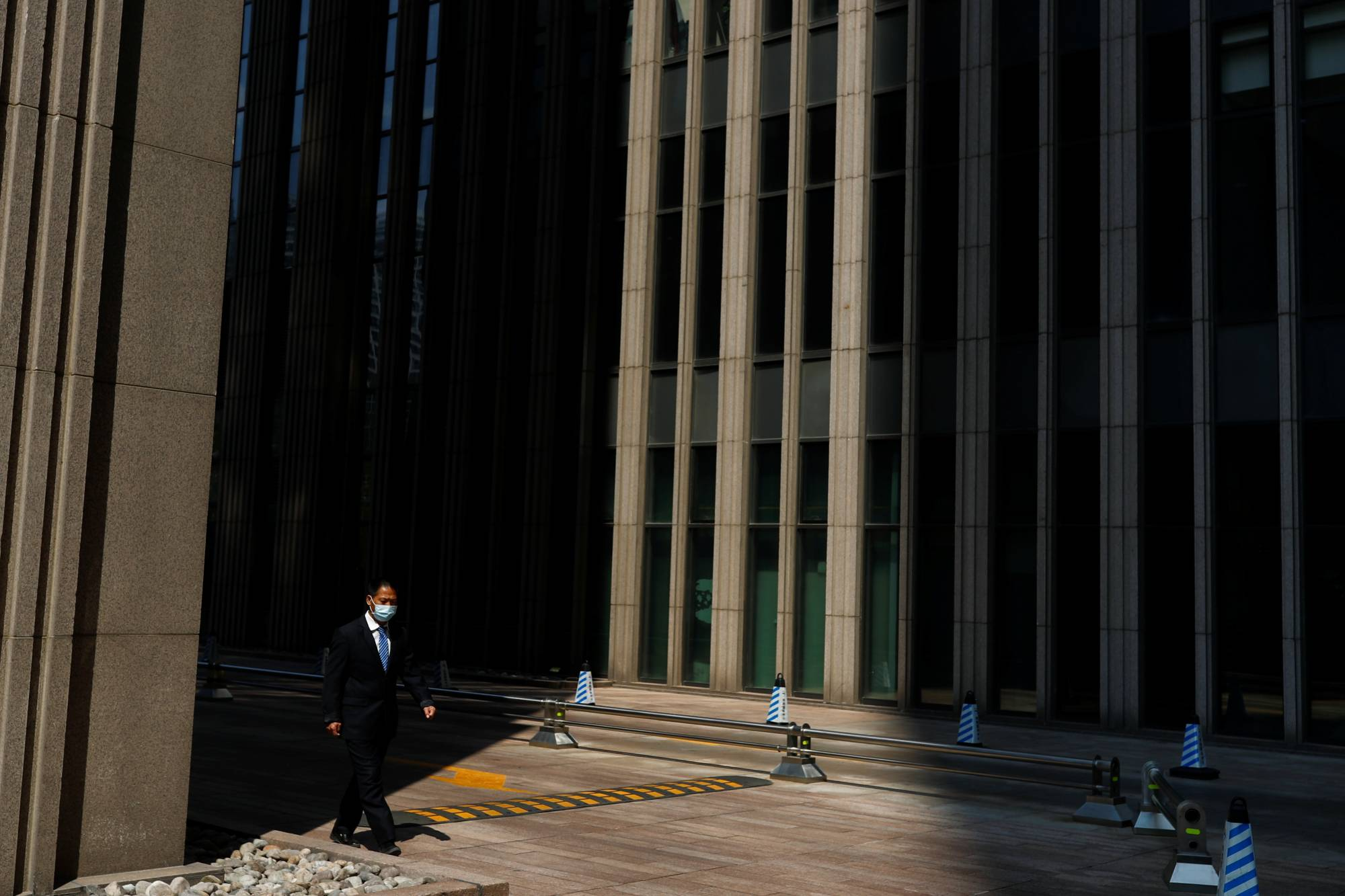 A businessman walks by Beijing's Central Business District on Friday. | REUTERS