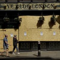 People walk past the boarded up 'Ye Olde London' pub in London, as cafes, pubs and restaurants remain closed in Britain during the lockdown to try and stop the spread of coronavirus, | AP