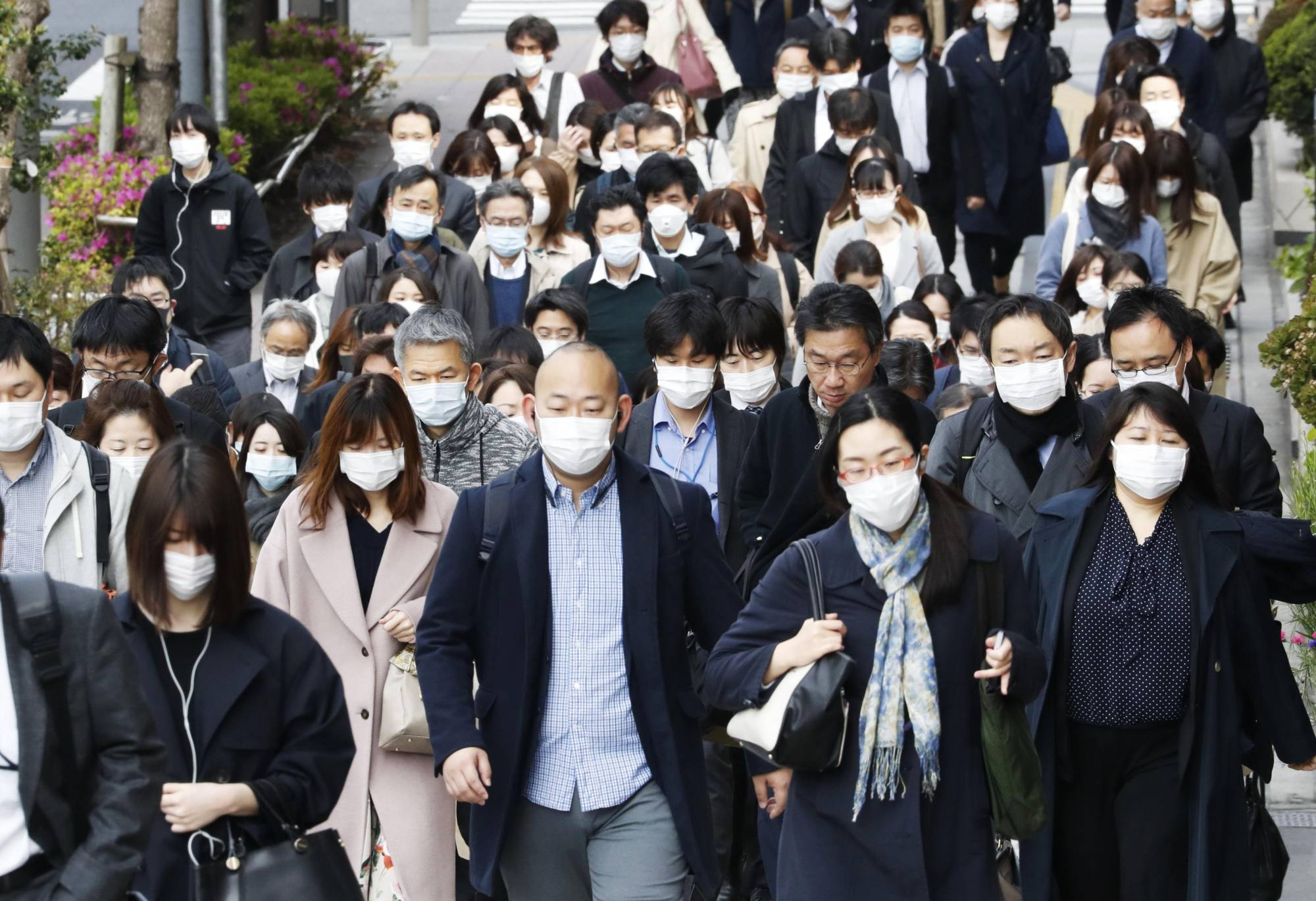 People wearing face masks head to work in Tokyo's Chuo Ward on Friday amid the spread of the new coronavirus. | KYODO
