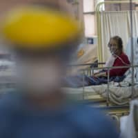 A patient using an oxygen mask rests inside the intensive care unit for people infected with the new coronavirus, at the 2 de Mayo Hospital in Lima on Friday.   AP