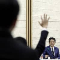 Prime Minister Shinzo Abe takes a question from a journalist during a news conference in Tokyo on Friday. | BLOOMBERG