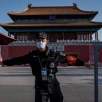 A security guard closes a gate outside the Forbidden City in Beijing on April 12.   AFP-JIJI