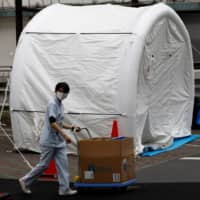 Medical workers walk by tents set up to test for the new coronavirus at Kawakita General Hospital in Tokyo on Friday. | REUTERS
