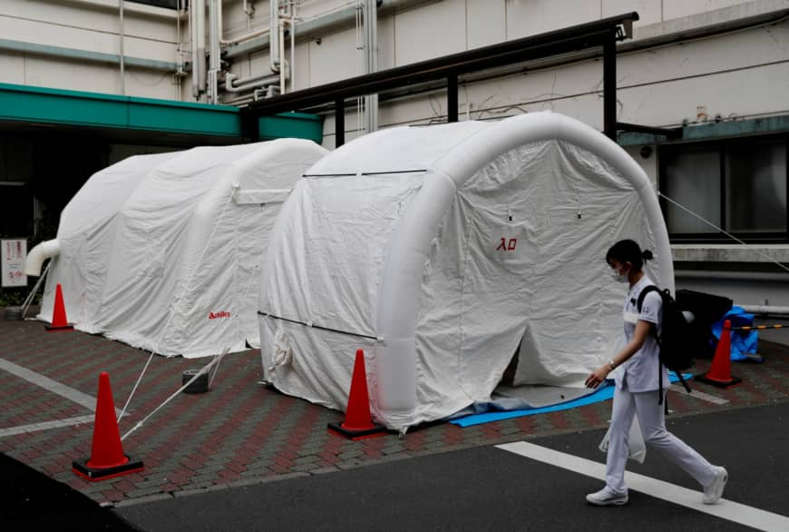A medical worker walks by tents set up to test for the new coronavirus at Kawakita General Hospital in Tokyo on Friday. | REUTERS