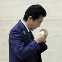 Prime Minister Shinzo Abe puts on a protective mask as he departs a news conference in Tokyo on Friday. | BLOOMBERG