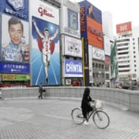A woman bicycles through Osaka's usually crowded Dotonburi area on Saturday, the first weekend after a nationwide state of emergency was declared over the new coronavirus. While prefectural governors have agreed on some measures to combat the virus, the issue of business closures and financial aid remains contentious.  | KYODO