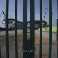 Manchester City's Etihad Stadium sits behind locked gates on April 9 in Manchester, England. | AP