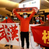 Supporters of Chinese Super League club Wuhan Zall greet the team as it arrives at the railway station in Wuhan, China, on Saturday.   AFP-JIJI