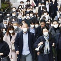 Commuters wearing masks walk in Tokyo's Chuo Ward on Friday morning.  Japanese expert Kentaro Iwata, who has criticized the country's response to the COVID-19 pandemic, warned Monday that he is 'pessimistic' over whether it will be possible to hold the postponed Olympics even in 2021. | KYODO