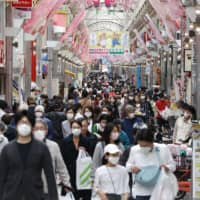People fill a shopping street in the Musashikoyama district of Shinagawa Ward, Tokyo, on Sunday afternoon. | KYODO
