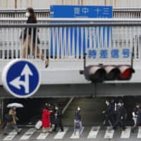 Commuters walk in a normally crowded area in Osaka's Umeda district on Monday morning. | KYODO