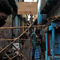 Men walk past a makeshift barricade meant to stop people from entering an area on April 9 during a nationwide lockdown in India to slow the spread of COVID-19, in Dharavi, one of Asia's largest slums. | REUTERS