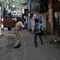 A policeman wields his baton toward a man for breaking curfew during a nationwide lockdown in India on April 11. | REUTERS