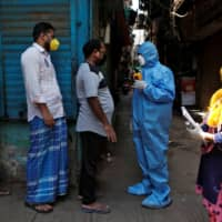 A doctor wearing a hazmat suit and a mask checks the temperatures of residents with an infrared thermometer, in Dharavi on April 11. | REUTERS