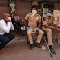 A man holds his ears while doing squats as part of a punishment imposed by the police for breaking a nationwide lockdown in Dharavi on April 11.  | REUTERS