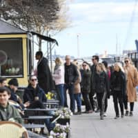 People line up to buy ice cream in Stockholm on Sunday. Sweden's death rate from COVID-19 is considerably higher than that of its Nordic neighbors. | TT NEWS AGENCY / VIA REUTERS