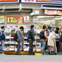 People wait in line in front of a drugstore in Tokyo to buy masks on April 6. | KYODO