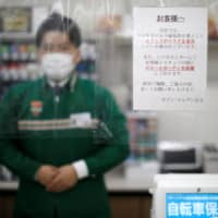 Plastic curtains at checkout counters to prevent COVID-19 infections are seen at a 7-Eleven store in Tokyo on April 13.   REUTERS