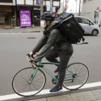 An Uber Eats staffer delivers food in Sendai, Miyagi Prefecture, earlier this month. | KYODO