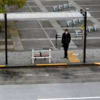 A lone man stands at a bus stop in front of Shinagawa Station in Tokyo on Monday.