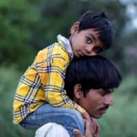 Dayaram Kushwaha, a migrant worker, carries his 5-year-old son, Shivam, on his shoulders as they walk along a road to return to their village during a nationwide lockdown in New Delhi. | REUTERS