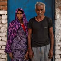 Kesra (left) and Takur Das, migrant workers and parents of Dayaram Kushwaha, pose for a portrait. | REUTERS