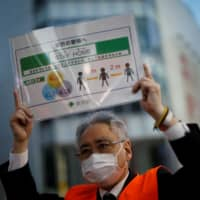 A Tokyo Metropolitan Government official holds up a placard as he calls for people to stay home and keep social distancing, at an entertainment district in Tokyo in April.   REUTERS