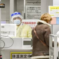 An official in protective gear at Narita Airport checks passengers arriving from South Korea on March 9. | KYODO