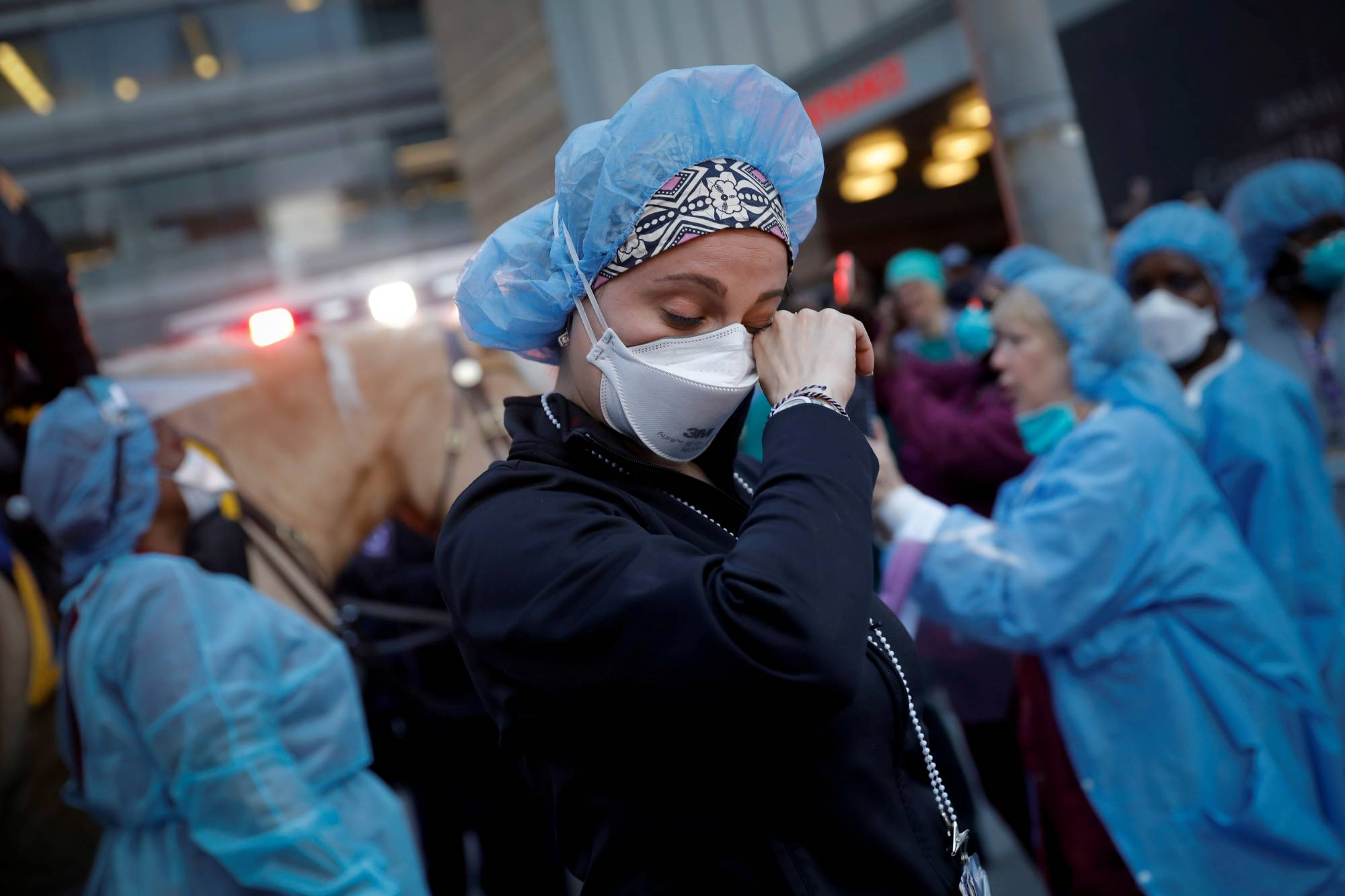 A nurse wipes away tears outside NYU Langone Medical Center in Manhattan as police officers cheer and thank health care workers last Thursday.    REUTERS