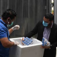Salvadoran Health Minister Francisco Alabi supervises the delivery of bottles of hydroxychloroquine pills to be distributed in hospitals in San Salvador on Tuesday. | AFP-JIJI