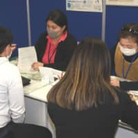 Officials at a public employment security office in Suzuka, Mie Prefecture, help foreign nationals seeking support. | CHUNICHI SHIMBUN
