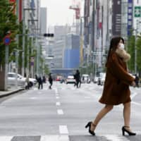 Fewer people than usual walk in the Ginza shopping district of Tokyo on Tuesday amid the COVID-19 pandemic. | KYODO