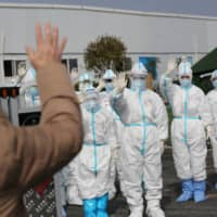 Medical personnel wave to a patient being discharged from the Leishenshan Hospital after recovering from the novel coronavirus in Wuhan, China, on March 1.  | CHINA DAILY / VIA REUTERS